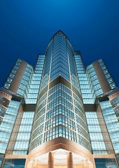 저녁 빛에 비즈니스 지구에 있는 현대적인 고층 빌딩의 밑면. 3d 렌더링.