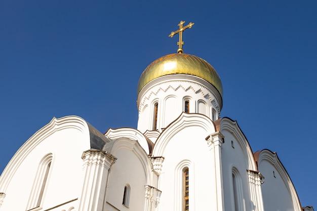 澄んだ青い空を背景に太陽に照らされた金色のドームと白い正教会の底面図