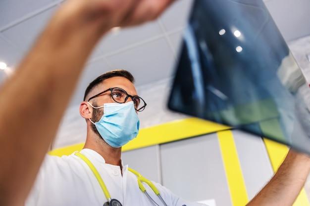 Вид снизу на молодого преданного врача, держащего рентгеновский снимок легких пациента и смотрящего на него.