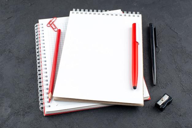 Vista dal basso per ufficio ripieni blocchi note penne rosse e nere temperamatite su sfondo scuro