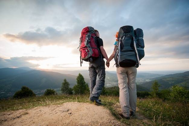 Bottom view pair with backpacks holding hands hiking on the ridge of hill, enjoying the view of beautiful mountains and incredible cloudy sky at sunset