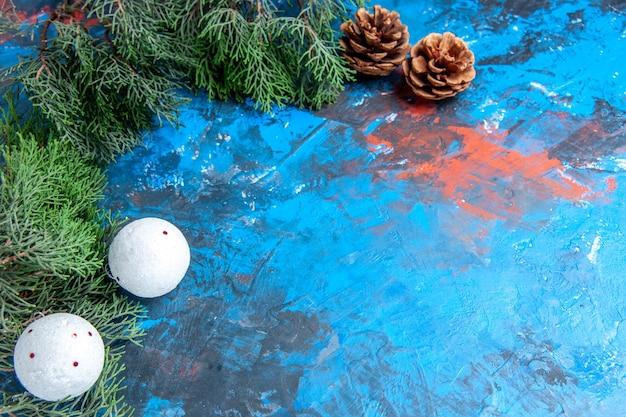 Vista dal basso rami di pino pigne palle di albero di natale bianco su sfondo blu-rosso con spazio di copia