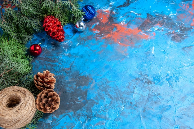 Bottom view pine tree branches with pinecones and colorful xmas tree toys straw thread on blue-red with free space