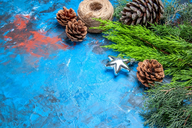 Bottom view pine tree branches with pinecones straw thread on blue-red background free space