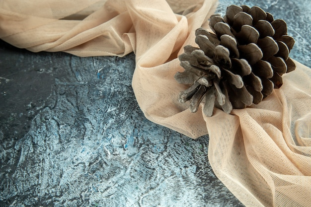 Bottom view pinecones on beige shawl on dark surface copy place