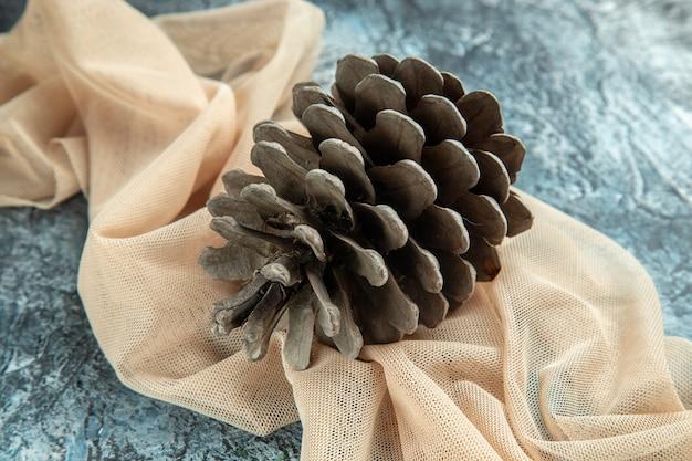 Bottom view pinecones on beige shawl on dark surface