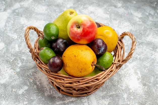 Vista dal basso in plastica cesto di vimini con mele pere feykhoas prugne e cachi sul tavolo grigio con spazio di copia