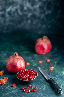 Bottom view pomegranate seeds bowl pomegranates knife on dark
