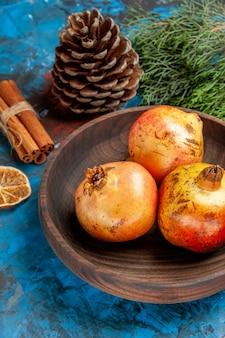 木のボウルの松の木の枝の木製プレートザクロの種子の底面図ザクロと青い背景のコーン乾燥レモンスライスシナモン