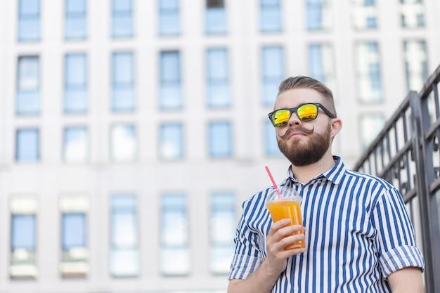 Портрет взгляда снизу стильного молодого мужчины битника в зеркальных очках с соком на бизнес-центре. городской праздник в концепции выходных.