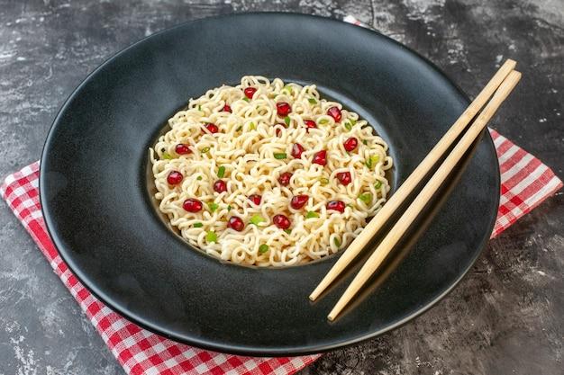 Vista dal basso ramen noodles bacchette su piatto nero tovaglia a quadretti rossa e bianca sul tavolo scuro
