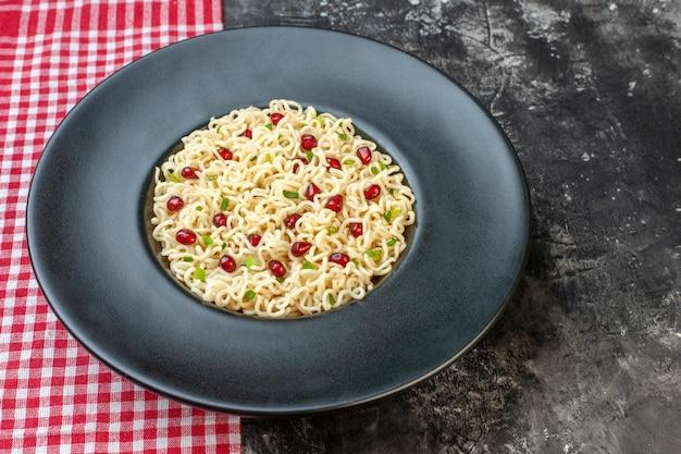 Tagliatelle di ramen vista dal basso su piatto rotondo scuro tovaglia a quadretti rossa e bianca su tavolo scuro