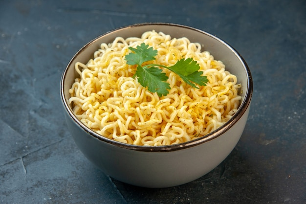 Bottom view ramen noodles with coriander in bowl on dark table