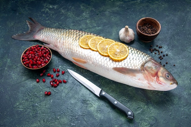 Bottom view raw fish black pepper pomegranates seeds in bowls garlic knife on table