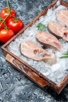 Fette di pesce crudo vista dal basso con ghiaccio su tavola di legno pomodori freschi sul tavolo