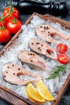 Fette di pesce crudo vista dal basso con ghiaccio su tavola di legno pomodori macinapepe sul tavolo
