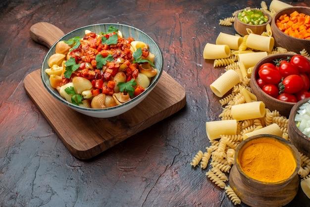 Вид снизу сырые макароны penne rigatoni спирали нарезанные овощи и куркума в мисках вкусная паста с томатным соусом в миске на деревянной доске на деревянном столе