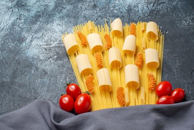 Вид снизу сырые пасты ригатони спагетти спирали помидоры черри фиолетовый платок на сером фоне