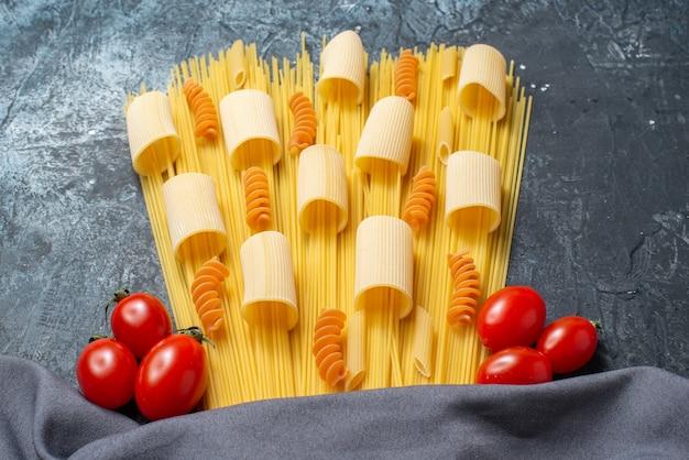 Вид снизу сырые пасты ригатони спагетти спирали помидоры черри фиолетовый платок на сером столе