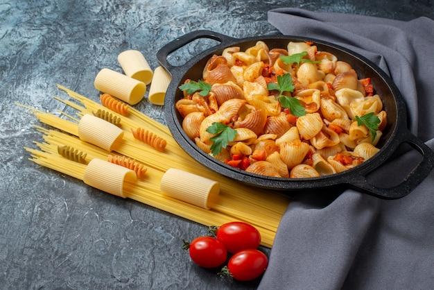 Вид снизу сырые макароны спагетти ригатони спирали вкусные макароны на сковороде помидоры черри на сером фоне