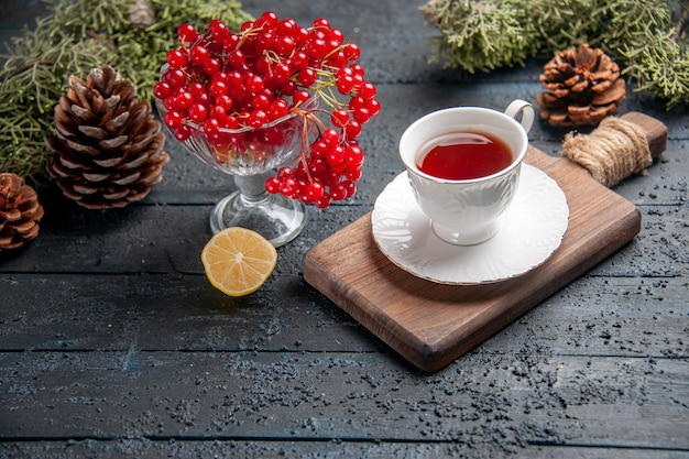 Bottom view red currant in a glass a cup of tea on chopping board slice of lemon pinecones on dark wooden background