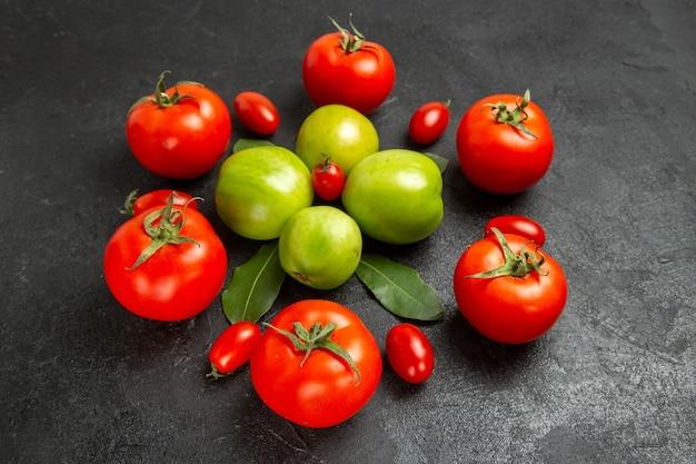 Vista dal basso rosso verde e pomodorini e foglie di alloro su sfondo scuro