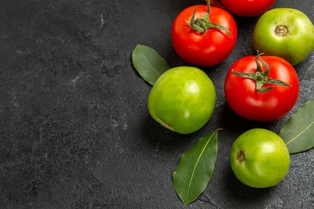 Vista dal basso pomodori rossi e verdi e foglie di alloro su sfondo scuro