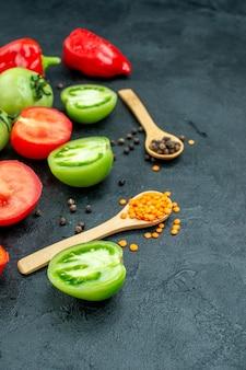 Vista dal basso pomodori rossi e verdi tagliati peperoni pepe nero lenticchie rosse accoglienti in cucchiai di legno sul tavolo scuro
