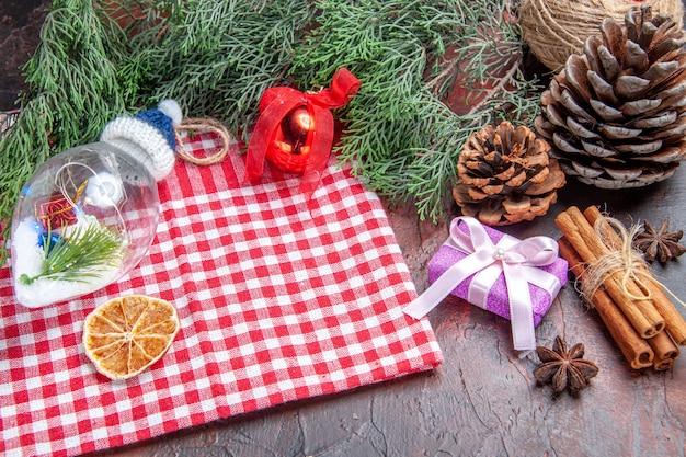 Vista dal basso rosso e bianco tovaglia a scacchi pino rami pigne regalo di natale cannella albero di natale giocattoli anice su sfondo rosso scuro