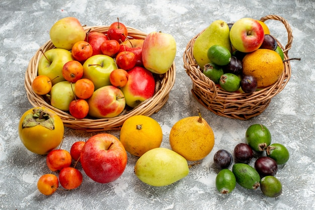 Vista dal basso mele rosse e gialle e prugne pere feykhoas e cachi nei cesti di vimini e anche sul terreno