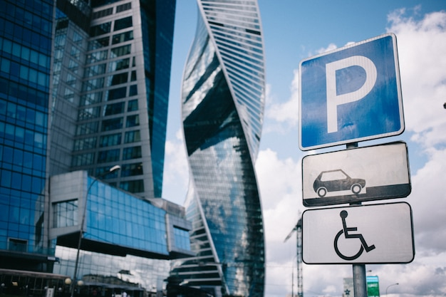 Bottom view of road signs parking, places for disabled, moscow-city skyscrapers