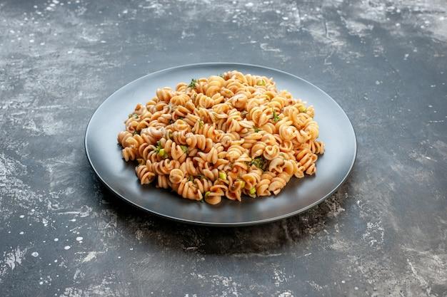 어두운 테이블에 둥근 접시에 하단보기 rotini 파스타