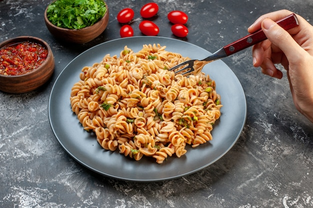 Bottom view rotini pasta on plate fork in female hand chopped greens and tomato sauce in bowls on grey table