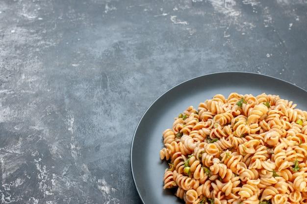 Bottom view rotini pasta on round plate on dark surface free space