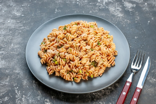 Bottom view rotini pasta on round plate fork and knife on dark table