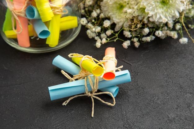 Вид снизу свиток цветные бумаги с пожеланиями в банке букет цветов на темном фоне