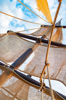 Bottom view of a ship mast with beige sails