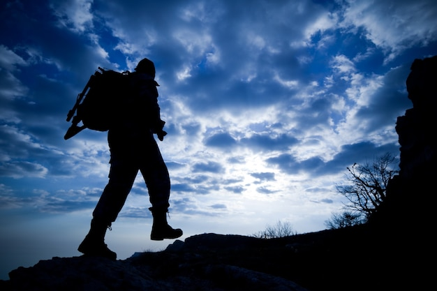 Bottom view silhouette of a male traveler with a backpack climbs up the mountains against a blue sky in white clouds. concept of the unknown and lovers of mountain tourism