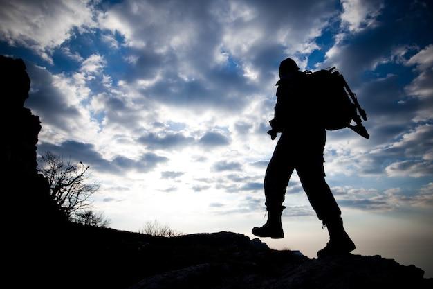 バックパックを持った男性旅行者の底面図のシルエットは、白い雲の青い空を背景に山を登る