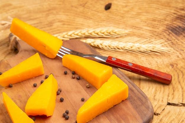 Vista dal basso fette di formaggio pepe nero e forchetta su tagliere pane a spiga di grano su superficie di legno