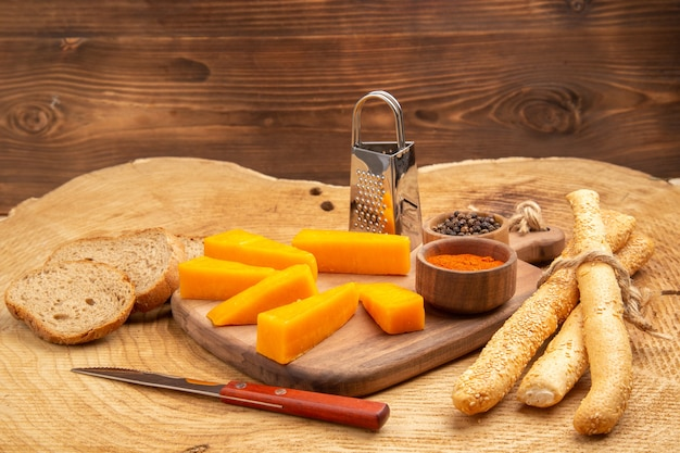 Bottom view slices of cheese box grater different spices in small bowls on cutting board knife bread on wooden ground