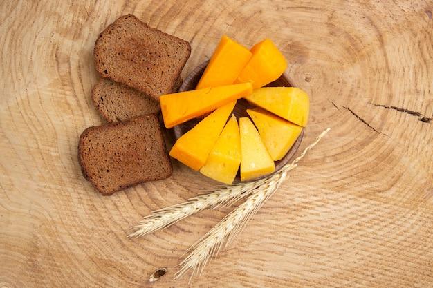 Vista dal basso fette di formaggio fette di pane integrale spiga di grano su tavola di legno