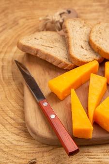Vista dal basso fette di formaggio fette di coltello da pane sul tagliere su superficie di legno
