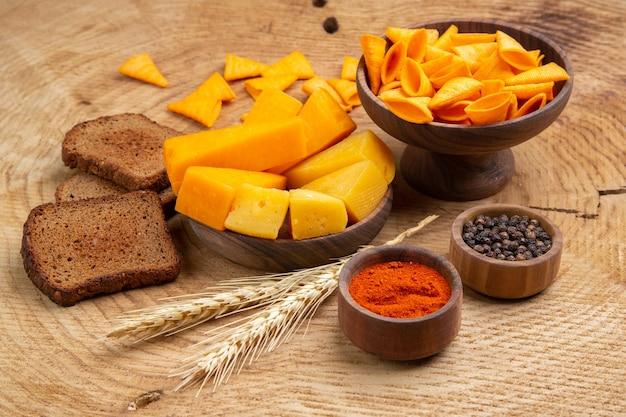 Vista dal basso fette di formaggio fette di pane di grano trucioli pepe nero peperone rosso in polvere in piccole ciotole sul tavolo di legno