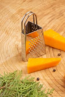 木製のテーブルにチーズが散らばった黒胡椒おろし金松の木の枝の底面図スライス