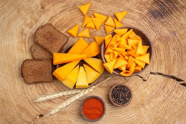 Вид снизу ломтики сыра, ломтики хлебных чипсов, разбросанных из миски колосья пшеницы, черный и красный перец на деревянном столе