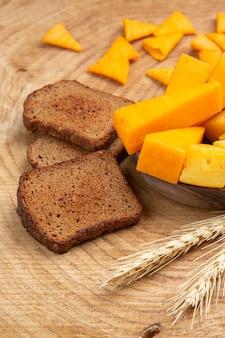 나무 테이블에 빵 밀 스파이크의 치즈 조각의 하단보기 조각