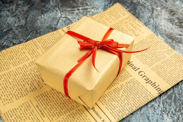 Bottom view small gift tied with red ribbon on newspaper on dark background