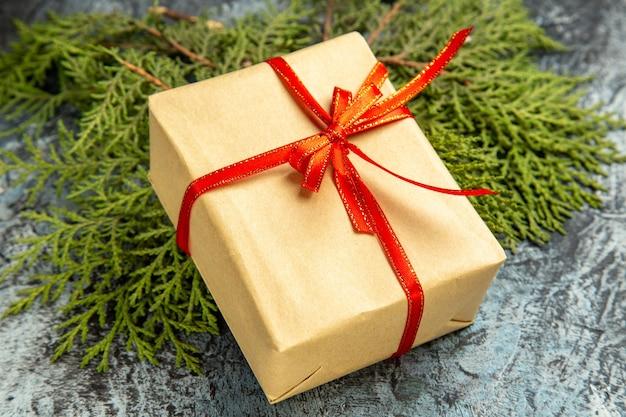 Vista dal basso piccolo regalo legato con nastro rosso su rami di pino su oscurità