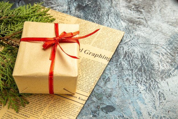 Bottom view small gift tied with red ribbon pine branches on newspaper on dark background copy space